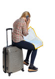 Vue arrière de voyageuse de femme se reposant sur leurs valises et recherchant une carte d'itinéraire, parlant le téléphone Images stock