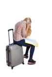 Vue arrière de voyageuse de femme se reposant sur leurs valises et recherchant une carte d'itinéraire, parlant le téléphone Photos libres de droits