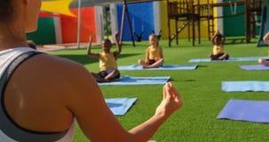 Vue arrière des écoliers de enseignement de professeur féminin pour exécuter le yoga dans le terrain de jeu 4k d'école banque de vidéos