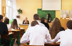 Vue arrière des étudiants écoutant l'étudiante près du bureau Image stock