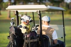 Vue arrière des amis de golfeur s'asseyant dans le boguet de golf Images stock