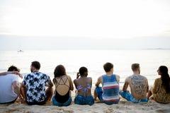 Vue arrière des amis divers s'asseyant à la plage ensemble Image stock