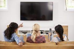 Vue arrière des amis féminins s'asseyant sur Sofa Watching Television Image stock