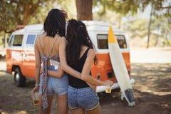 Vue arrière des amis féminins tenant la bière en le fourgon Photos stock