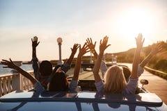Vue arrière des amis heureux conduisant le cabriolet avec les mains augmentées Images libres de droits