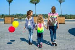 Vue arrière des amis marchant ensemble dans la ville Image libre de droits