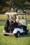 Vue arrière des amis masculins de golfeur s'asseyant dans le boguet de golf Image libre de droits