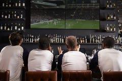 Vue arrière des amis masculins observant le jeu dans la barre de sports Photos libres de droits