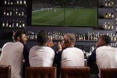 Vue arrière des amis masculins observant le jeu dans la barre de sports Photographie stock libre de droits