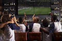 Vue arrière des amis observant le jeu dans la célébration de barre de sports photo stock