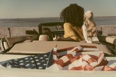 vue arrière des amis s'asseyant dans la voiture avec le drapeau américain au bord de la mer Photographie stock