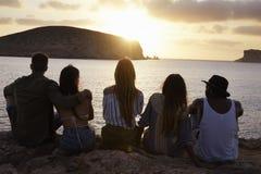 Vue arrière des amis s'asseyant sur Cliff Watching Sunset Photo stock