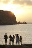 Vue arrière des amis se tenant sur Cliff Watching Sunset Image stock
