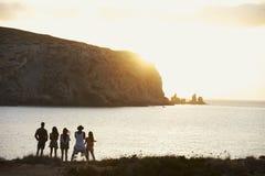 Vue arrière des amis se tenant sur Cliff Watching Sunset Photographie stock