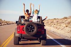 Vue arrière des amis sur le voyage par la route conduisant dans la voiture convertible Images libres de droits