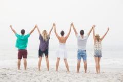 Vue arrière des amis tenant des mains et la position dans une rangée Photographie stock libre de droits
