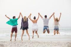 Vue arrière des amis tenant des mains et sautant sur la plage Photo libre de droits