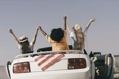 vue arrière des amis tenant des mains tout en se reposant dans la voiture avec le drapeau américain au bord de la mer Photo libre de droits