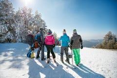 Vue arrière des amis des vacances d'hiver sur le dessus de montagne Image stock