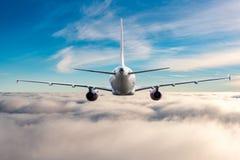 Vue arrière des avions en vol L'avion de passagers vole haut au-dessus des nuages et du ciel bleu Voyage d'affaires et Images libres de droits