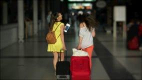 Vue arrière des brunes étonnantes avec des bagages à l'aéroport Les femmes tiennent des documents et des billets dans leurs mains banque de vidéos