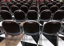 Vue arrière des chaises noires dans la rangée Photographie stock libre de droits