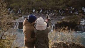 Vue arrière des couples de déplacement se tenant près des cascades en Islande le jour ensoleillé et prenant la photo de selfie su banque de vidéos