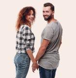 Vue arrière des couples heureux tenant des mains et regardant l'appareil-photo Photos stock