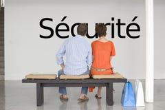 Vue arrière des couples lisant le sécurité français des textes (sécurité) et contemplant au sujet de la sécurité Photo stock
