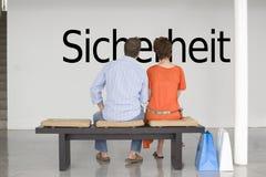Vue arrière des couples lisant le texte allemand Sicherheit (sécurité) et contemplant au sujet de la sécurité Image stock