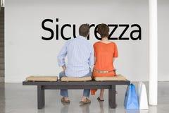 Vue arrière des couples lisant le texte italien Sicurezza (sécurité) et contemplant au sujet de la future sécurité Photographie stock libre de droits