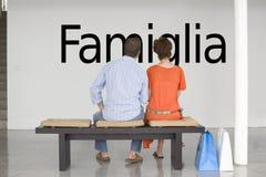 Vue arrière des couples posés sur le banc lisant le texte italien Famiglia (famille) sur le mur Photos stock