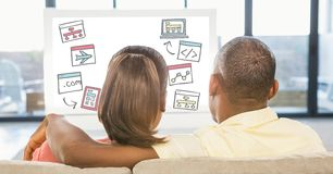 Vue arrière des couples regardant de diverses icônes sur le PC de bureau tout en se reposant à la maison Photographie stock libre de droits