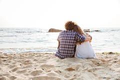 Vue arrière des couples se reposant et étreignant sur la plage Photos stock