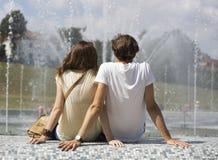 Vue arrière des couples se reposant sur le mur de fontaine Photographie stock libre de droits