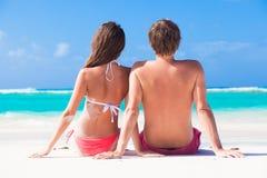 Vue arrière des couples se reposant sur une plage tropicale dedans Image libre de droits