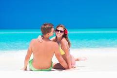 Vue arrière des couples se reposant sur une plage tropicale dedans Image stock