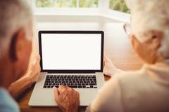 Vue arrière des couples supérieurs utilisant l'ordinateur portable Photo stock