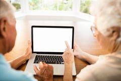 Vue arrière des couples supérieurs utilisant l'ordinateur portable Images libres de droits