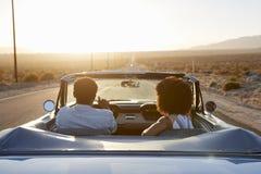 Vue arrière des couples sur le voyage par la route conduisant la voiture convertible classique vers le coucher du soleil image libre de droits