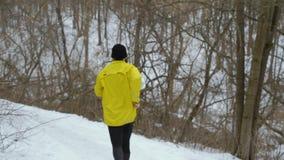 Vue arrière des débuts sportifs convenables d'homme fonctionnant en bas de la colline dans la forêt d'hiver banque de vidéos