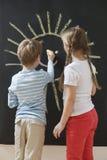 Vue arrière des enfants de mêmes parents dessinant le soleil sur le tableau noir Photo libre de droits