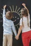 Vue arrière des enfants de mêmes parents dessinant le soleil sur le tableau noir tout en tenant des mains Image stock