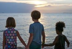 Vue arrière des enfants divers se tenant à la plage ensemble Photographie stock libre de droits