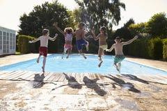 Vue arrière des enfants sautant dans la piscine extérieure Images stock