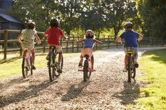 Vue arrière des enfants sur le tour de cycle dans la campagne ensemble Images libres de droits