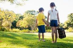Vue arrière des enfants tenant leurs mains semblant en avant tout en tenant un bagage Image libre de droits