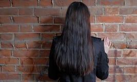 Vue arrière des femmes aux cheveux longs de brune contre le mur de briques rouge photographie stock libre de droits