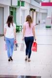 Vue arrière des femmes marchant dans le mail avec des paniers Photographie stock libre de droits
