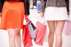 Vue arrière des femmes marchant dans le mail avec des paniers Image stock